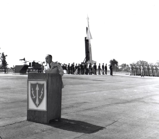 Ceremony marking activation of the first operational Nike-Hercules unit on the east coast at W-25 on Sept. 4, 1958. The firing unit is Battery B-1st Missile Battalion-562d Artillery. In the top photo, Army Vice Chief of Staff Lyman L. Lemnitzer delivers remarks at podium blazoned with ARADCOM insignia--yellow missile and lighting bolts on a red shield trimmed yellow. Note Nike-Ajax on launcher behind band in the background.